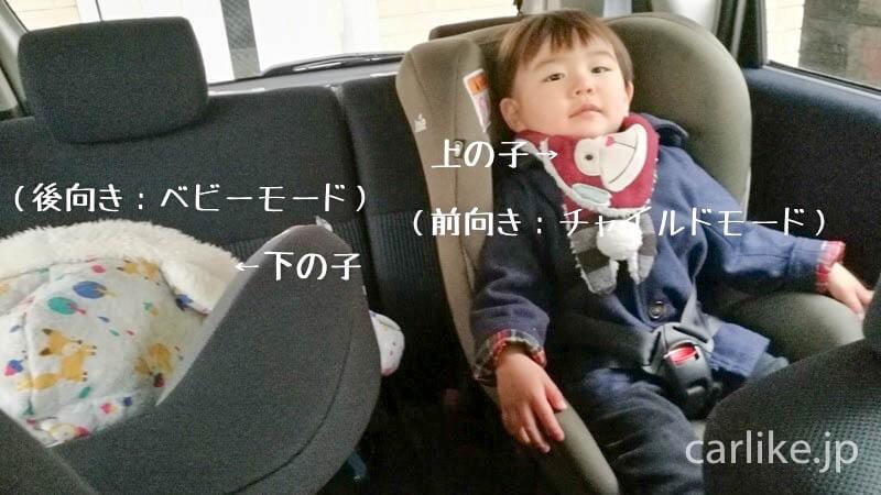 後部座席2台のチャイルドシートに座る子供